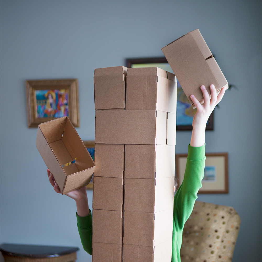7 year old stacking Nova Natural Jumbo Blocks above their head.