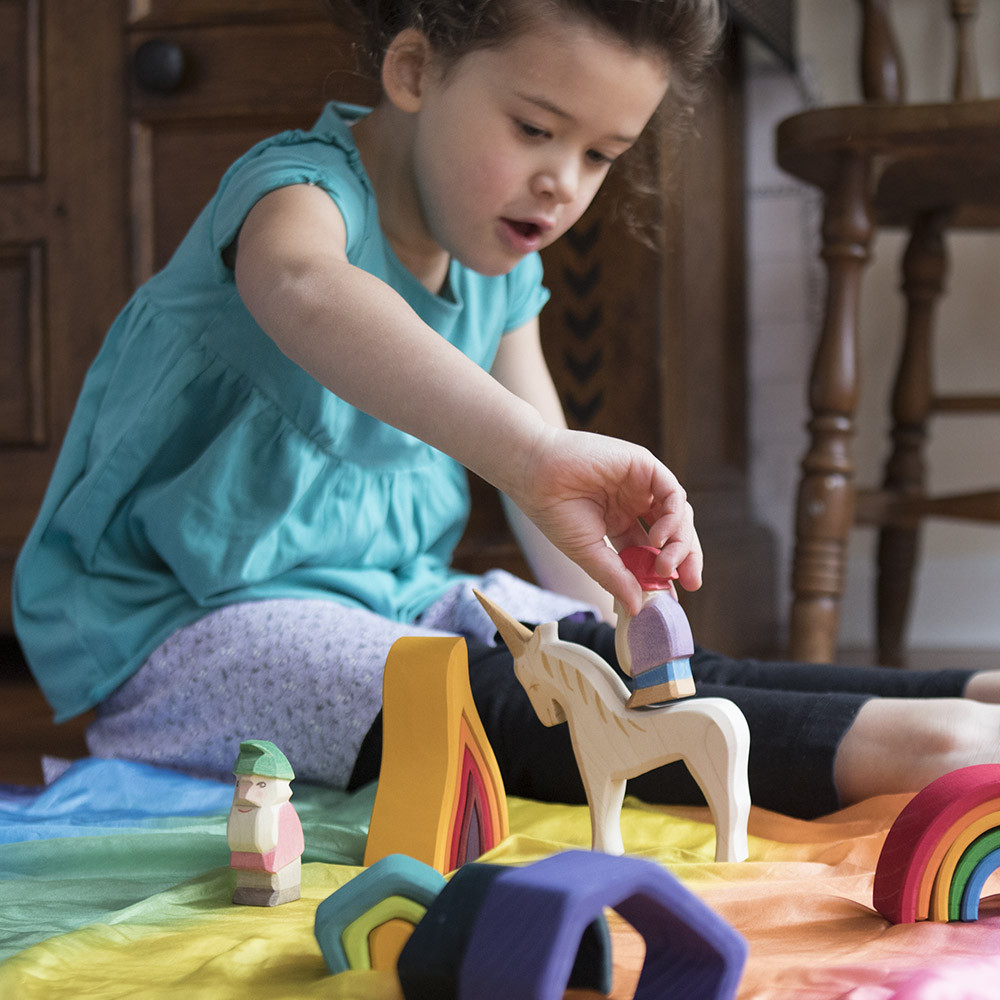Girl playing with a wooden unicorn and a Nova Natural Rainbow Playsilk.