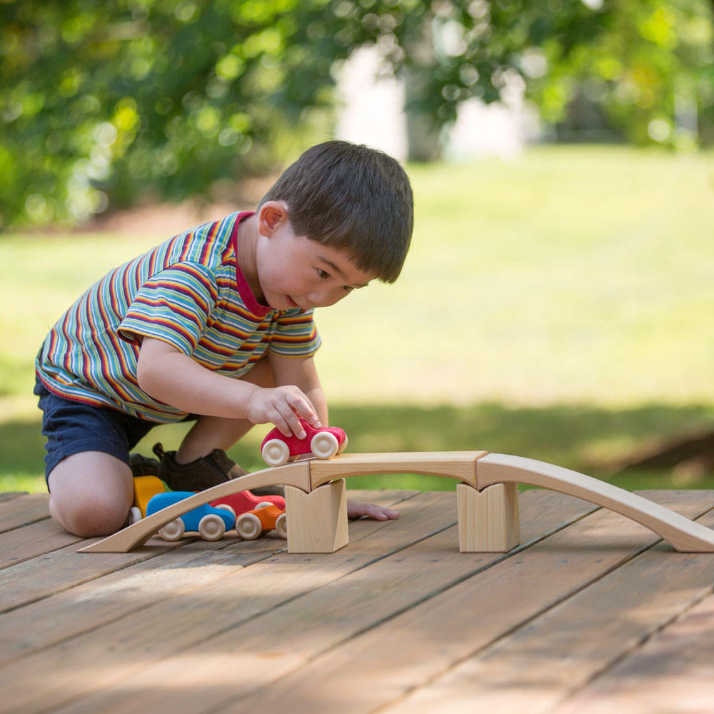 Little boy pushing wooden cars over a Nova Natural wooden bridge.